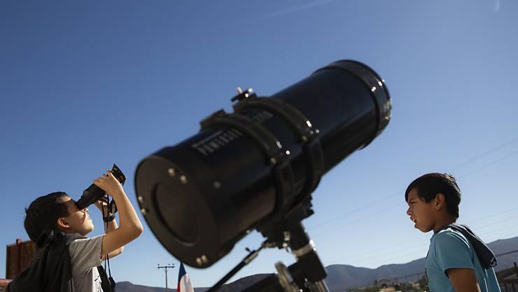 Auch Kinder in Chile testen Feldstecher, um die Sonnenfinsternis zu beobachten.