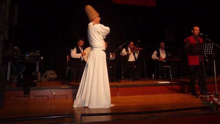 In Rotation: Einer der beiden Derwische auf der Bühne des Konzertsaals.