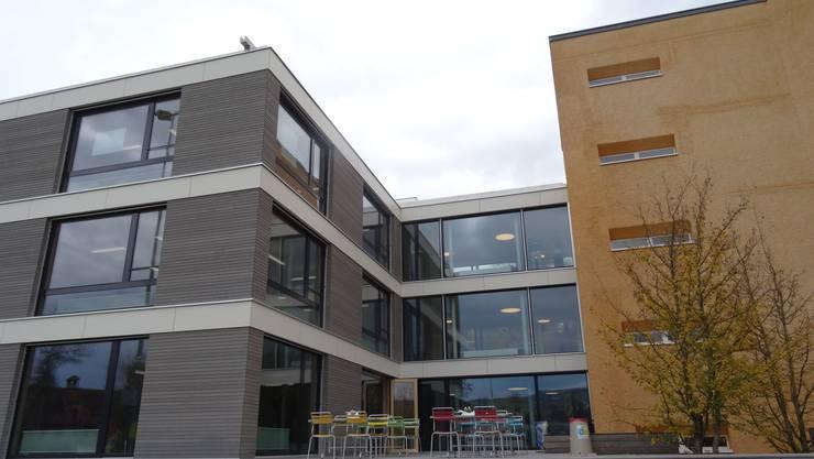 Übergang zwischen Alt- und Neubau des Schulhauses Allmend vom Sportplatz aus gesehen