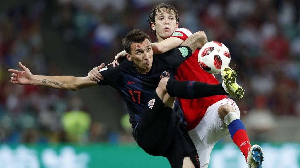 Croatia's Mario Mandzukic, left, challenges for the ball with Russia's Mario Fernandes during the quarterfinal match between Russia and Croatia at the 2018 soccer World Cup in the Fisht Stadium, in Sochi, Russia, Saturday, July 7, 2018. (AP Photo/Rebecca Blackwell)