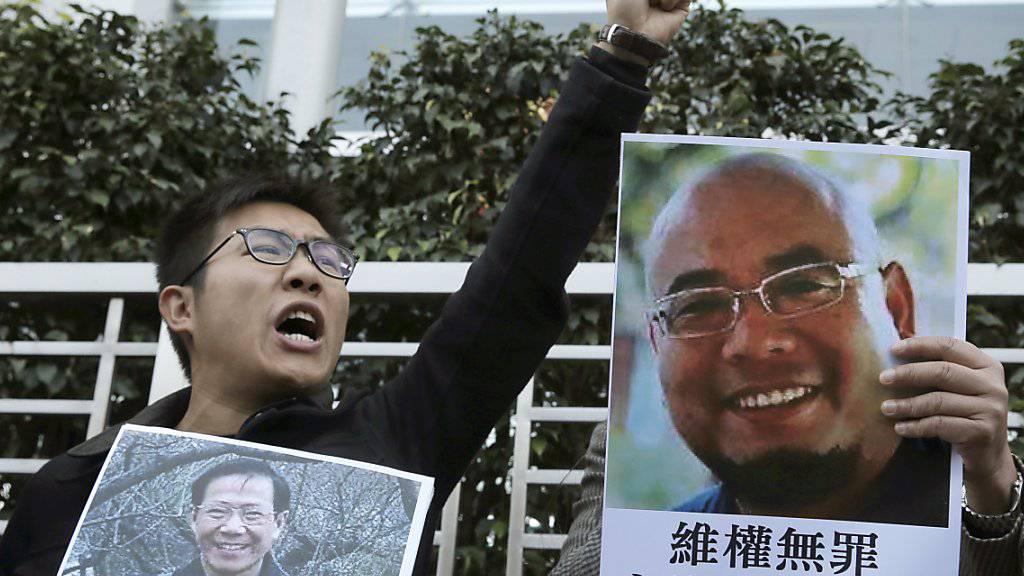 Aktivist in Hongkong mit den Konterfeis der chinesischen Dissidenten Qin Yongmin (l) und Wu Gan