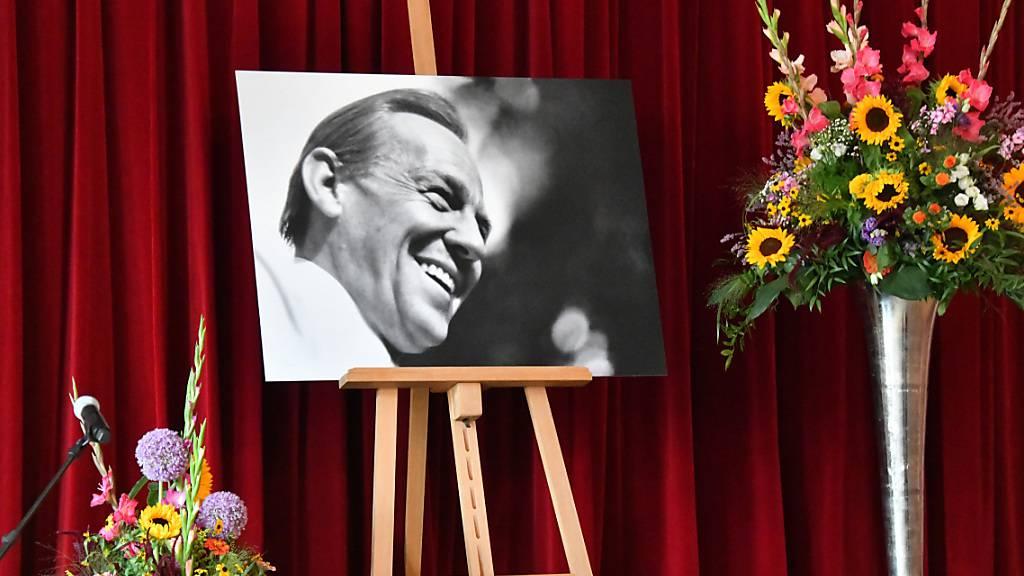 Ein Bild von Herbert Köfer steht bei der Trauerfeier der Stadt Beelitz auf der Bühne. Der Schauspieler starb am 24. Juli im Alter von 100 Jahren. Er wird in Beelitz beigesetzt. Für die Fans wird es am 27. August eine weitere Trauerfeier geben. Foto: Bernd Settnik/dpa