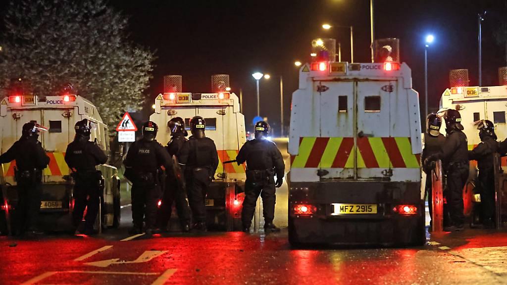 Polizisten stehen nach Unruhen auf einer Straße. In Nordirland ist es in der Osternacht erneut zu gewaltsamen Unruhen gekommen. Foto: Liam Mcburney/PA Wire/dpa