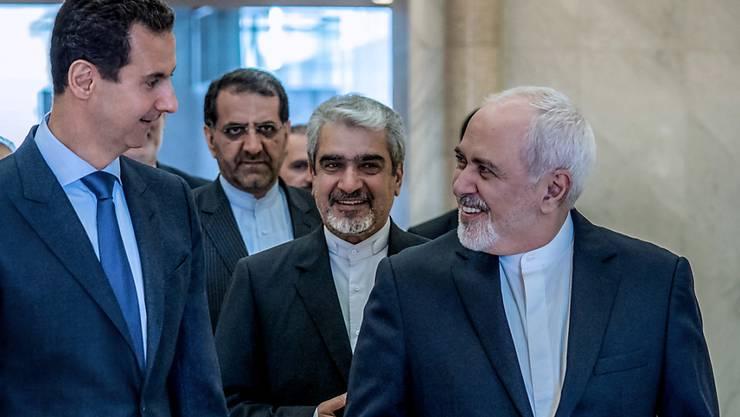 Der syrische Präsident Baschar al-Assad (l) und der iranische Aussenminister Mohammed Dschawad Sarif haben bei ihrem Treffen die kommende Woche anstehenden Gespräche in der kasachischen Hauptstadt Nur-Sultan besprochen.