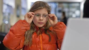 Ein Kind probiert eine Brille an (Archiv)