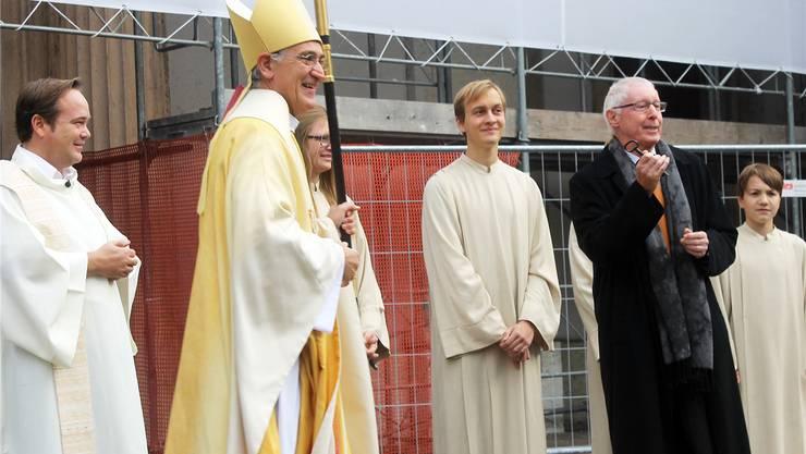 Die Sanierung kann beginnen: Vor der Stadtkirche geht der Schlüssel nach dem letzten Gottesdienst von Pfarrer Kai Fehringer (ganz links) via Bischof Harald Rein an den Vizepräsidenten der Baukommission, Kurt Stutz (rechts). jürg salvisberg