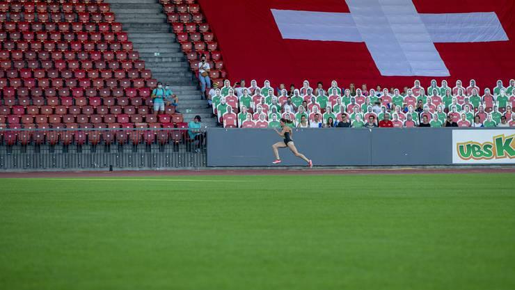Lea Sprunger läuft an den 1000 Pappfiguren vorbei, die neben den 300 Zuschauern Zugang zum Letzigrund erhalten haben.