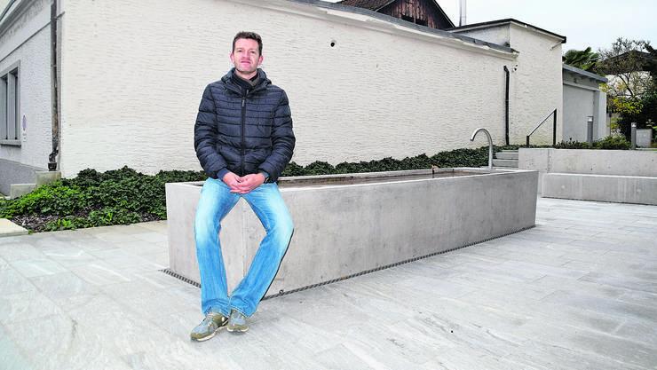 Anthony Paine sitzt auf der neusten Ergänzung seiner Karte, dem Brunnen vor dem Kantonalbanksgebäude in Bremgarten