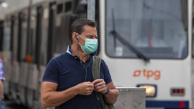 Ein Passant in Genf trägt eine Gesichtsmaske als Vorsichtsmassnahme gegen eine Ansteckung mit dem Coronavirus. (Archivbild)