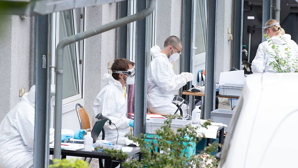 Mitarbeiter des Gesundheitsamtes sitzen an einer Corona-Teststrecke vor einem Studentenwohnheim in Dresden. Nach dem Tod eines an Covid-19 erkrankten Indien-Rückkehrers werden sämtliche Bewohner des Hochhauses auf das Coronavirus getestet.