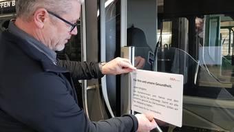 Peter Baertschiger, Geschäftsführer der Busbetrieb Aarau AG (BBA), montiert ein Corona-Infoplakat.