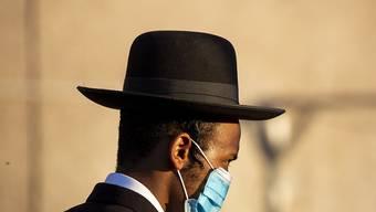Ein orthodoxer Jude wartet mit medizinischem Mundschutz darauf, eine Straße überqueren zu können. Landesweit sind coronabedingte Beschränkungen in Kraft getreten, nachdem die Zahl der Infizierten gestiegen ist. Foto: Ariel Schalit/AP/dpa