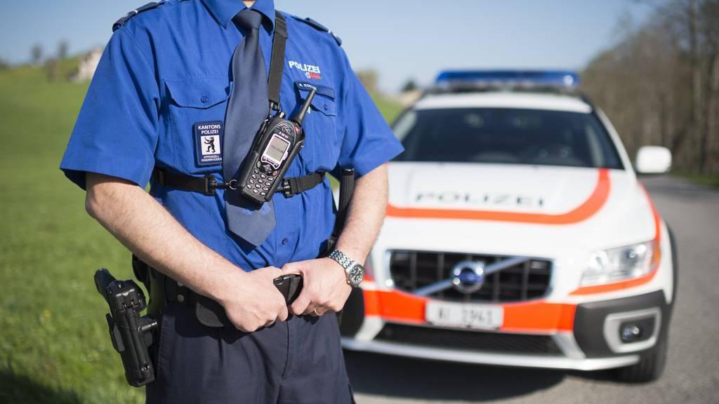 Ein Beamter der Kantonspolizei Appenzell Innerrhoden steht vor seinem Dienstfahrzeug. (Archiv)