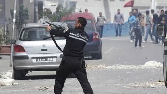 Polizist (vorne) und Demonstrierende in Tunis