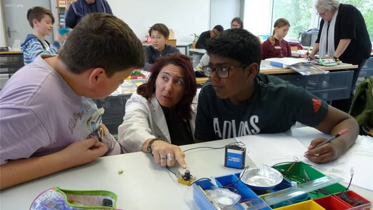Sandra Nachtigal im weissen Kittel erklärt zwei Schülern ein Experiment.