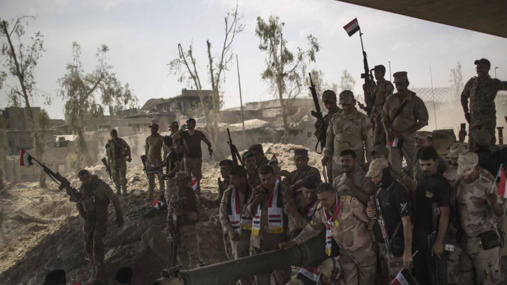 Irakische Soldaten feiern ihren Sieg über die Terrormiliz IS in der irakischen Stadt Mossul. Noch ist allerdings nicht klar, ob die Stadt vollständig befreit ist.