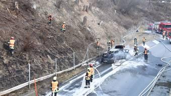 Die Feuerwehrleute mussten nicht nur den Autobrand löschen, sondern auch die Flammen auf der Böschung.