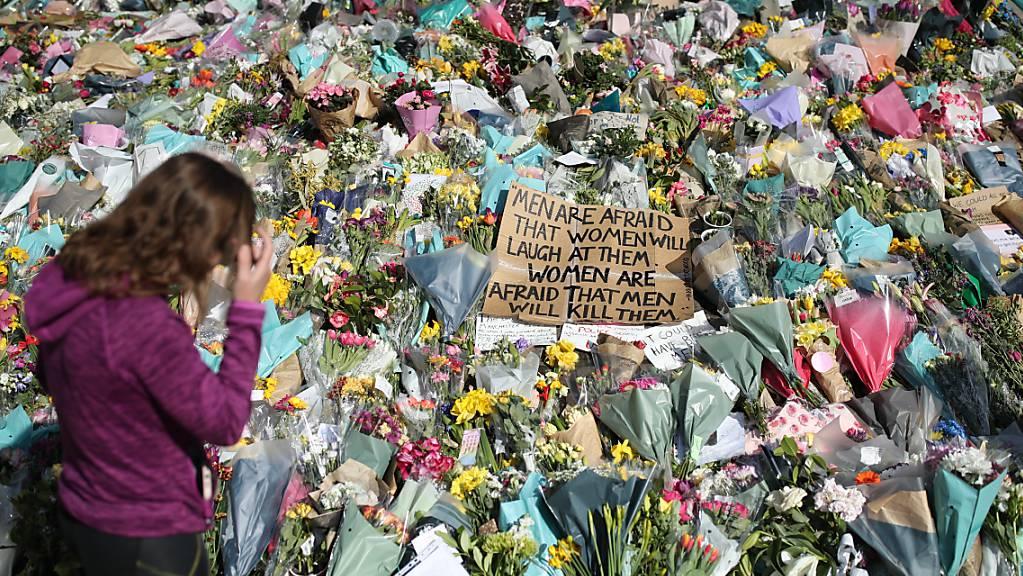 ARCHIV - Eine Frau schaut sich die Blumen an, die für die getötete Sarah Everard im Clapham Common Park niedergelegt wurden. (Archivbild) Foto: Yui Mok/PA Wire/dpa