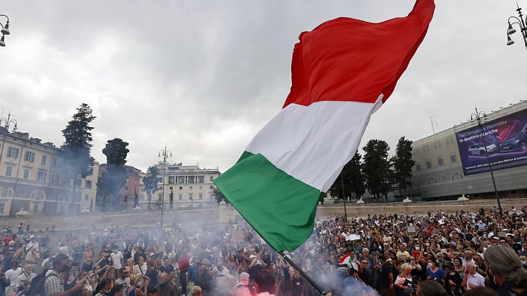 Demonstranten zünden bei einer Demonstration gegen den geplanten «grünen Pass» einen Bengalo. Foto: Riccardo De Luca/AP/dpa