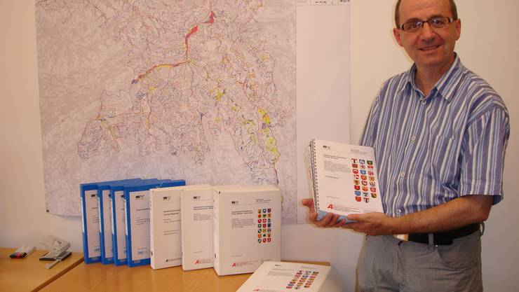 Projektleiter Martin Tschannen neben der Gefahrenkarte Hochwasser und einzelnen Teilplan-Paketen. Lü.