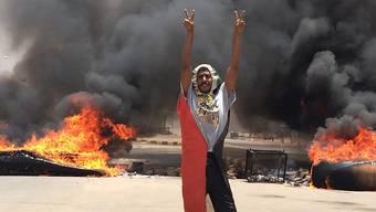 Ein Demonstrant in Khartum macht das Victory-Zeichen vor brennenden Reifen.