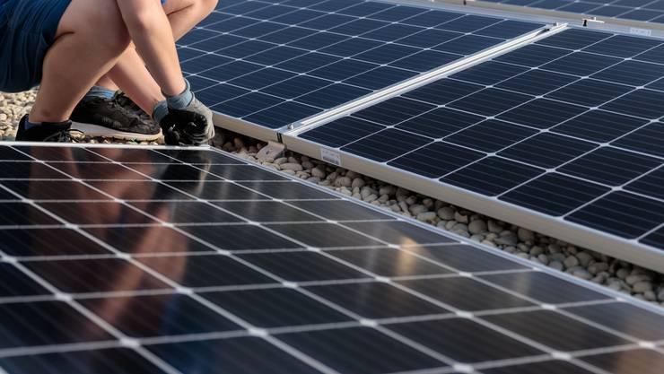 Eine Solaranlage wird auf einem Dach angebracht. (Symbolbild)
