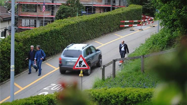 Weil entlang der Stationsstrasse kein Trottoir besteht, laufen viele Fussgänger die Fahrbahn hinunter.