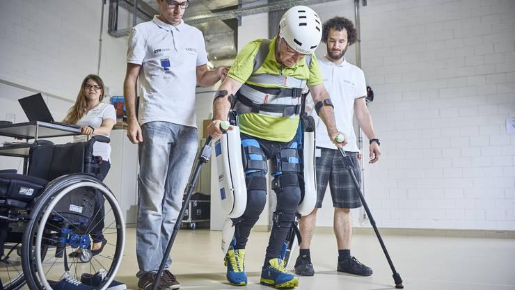 Werner Witschi sitzt im Rollstuhl. Hier trainiert er das Gehen mit einem Exoskelett.