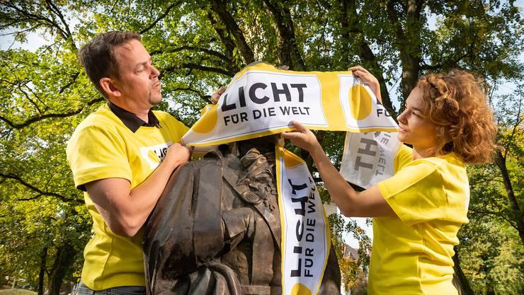Mitarbeiter von «Licht für die Welt» verhüllen der Statue von Tadeusz Koúciuszko die Augen.