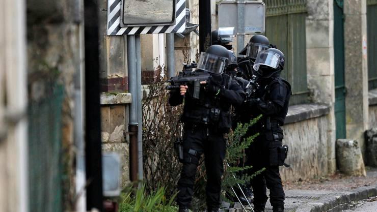 Polizisten durchsuchen Häuser in Longpont.