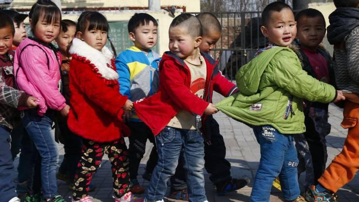 Chinesische Kinder auf dem Schulweg - verheirateten Paaren ist es künftig erlaubt, ein zweites Kind zu bekommen. (Symbolbild)