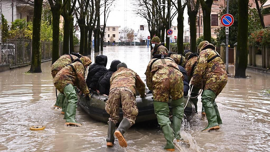 Männer schieben ein Boot inmitten einer überschwemmten Straße in einem Wohngebiet an. Die Wetterlage in Italien bleibt nach heftigen Niederschlägen vom Wochenende angespannt, etliche Familien mussten aus ihren Wohnungen evakuiert werden. Foto: Massimo Paolone/LaPresse via ZUMA Press/dpa