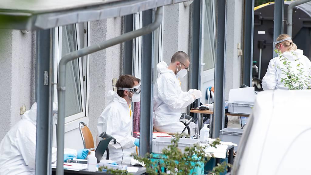 Mitarbeiter des Gesundheitsamtes sitzen an einer Corona-Teststrecke vor einem Studentenwohnheim in Dresden. Nach dem Tod eines an Covid-19 erkrankten Indien-Rückkehrers werden sämtliche Bewohner des Hochhauses auf das Coronavirus getestet. Foto: Sebastian Kahnert/dpa-Zentralbild/dpa Foto: Sebastian Kahnert/dpa-Zentralbild/dpa