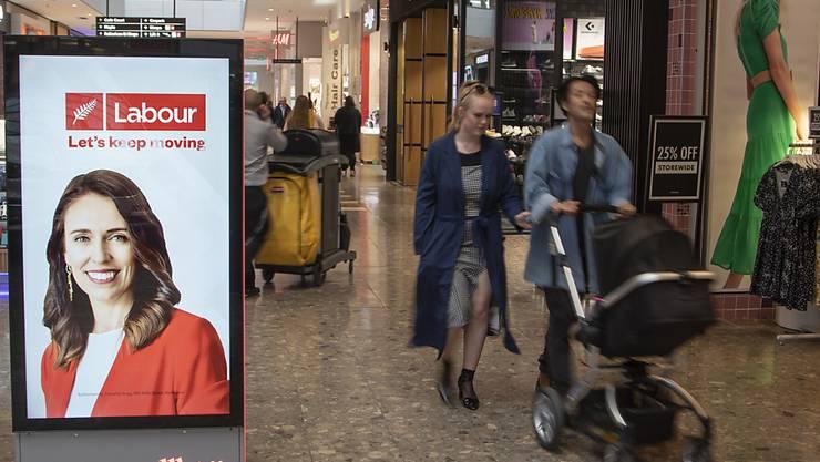 Menschen gehen in einem Einkaufszentrum an einer elektronischen Plakatwand vorbei, die ein Foto der neuseeländischen Premierministerin Jacinda Ardern zeigt. Neuseeländer gehen bei den Parlamentswahlen am Samstag, den 17.10.2020, an die Urnen. Foto: Mark Baker/AP/dpa