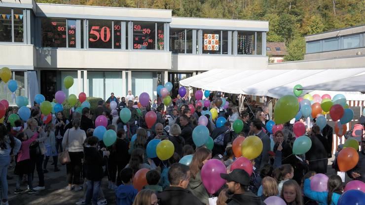 Vor den geschmückten Fenstern des Schulhauses warteten die Kinder und Gäste gespannt auf den Start des Ballonwettbewerbs.