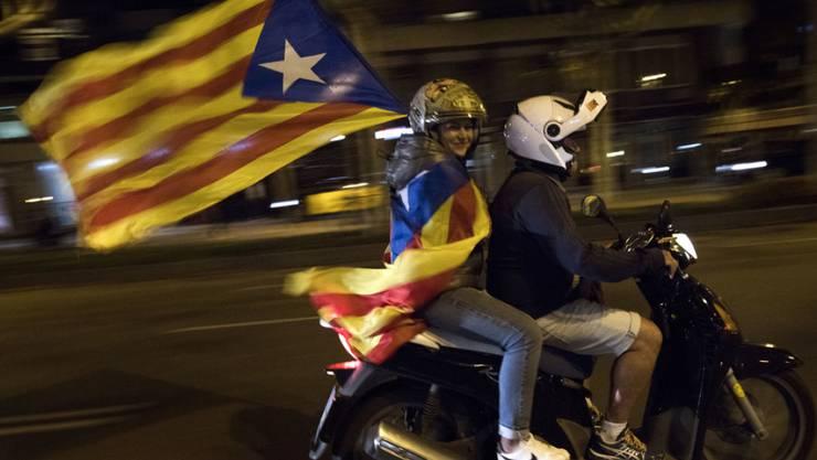 Eine Frau hält eine Flagge Kataloniens in den Händen. Der katalanische Regierungschef Puigdemont hat ein von der spanischen Zentralregierung gesetztes Ultimatum verstreichen lassen. Als Reaktion kündigt Madrid weitere Schritte zum Entzug der katalanischen Autonomie an. (Archiv)
