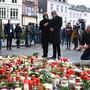 Malu Dreyer (SPD), Ministerpräsidentin von Rheinland-Pfalz, und ihr Ehemann Klaus Jensen stehen vor Blumen und Kerzen, die vor der Porta Nigra im Gedenken der Opfer der Amokfahrt eines 51-jährigen Mannes durch die Innenstadt niedergelegt wurden. Foto: Harald Tittel/dpa