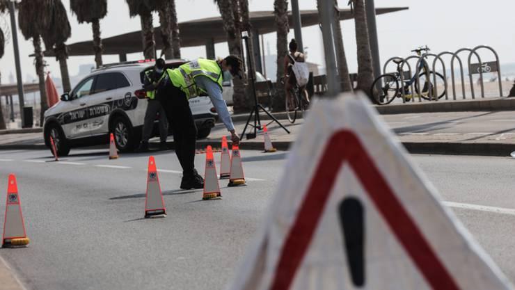 Polizeibeamte mit Mund-Nase-Schutz sperren eine Straße ab. Die israelische Regierung will mit einem zweiten landesweiten Lockdown eine weitere Ausbreitung des Coronavirus verhindern. Foto: Ilia Yefimovich/dpa