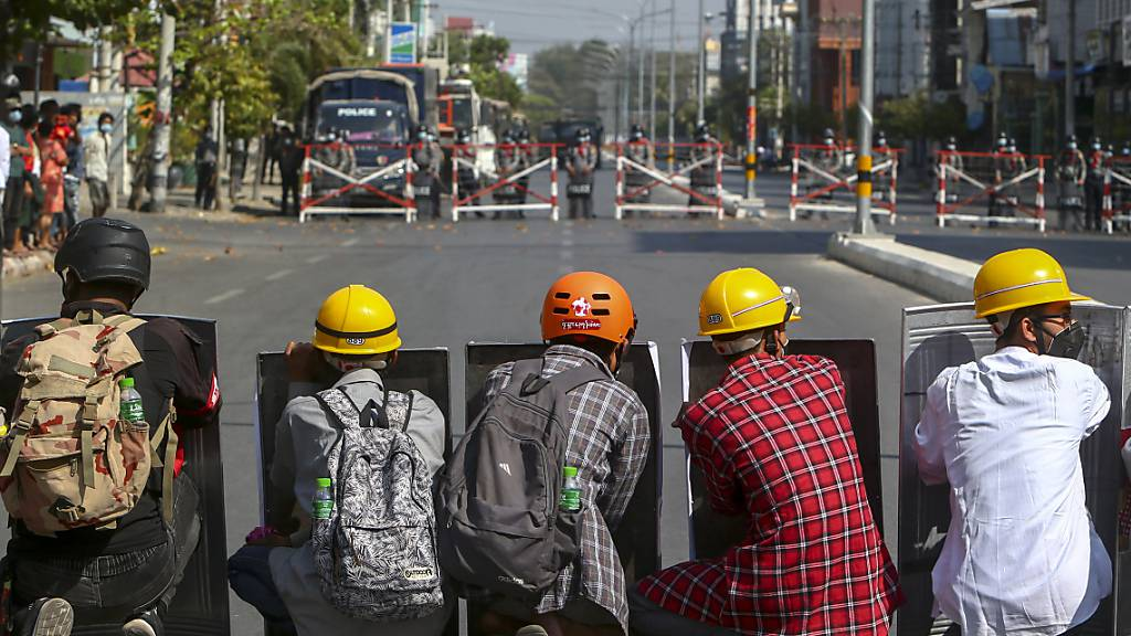 Demonstranten und Bereitschaftspolizisten stehen sich bei einem erneuten Protest gegen die Militärjunta in Mandalay gegenüber. Foto: Uncredited/AP/dpa