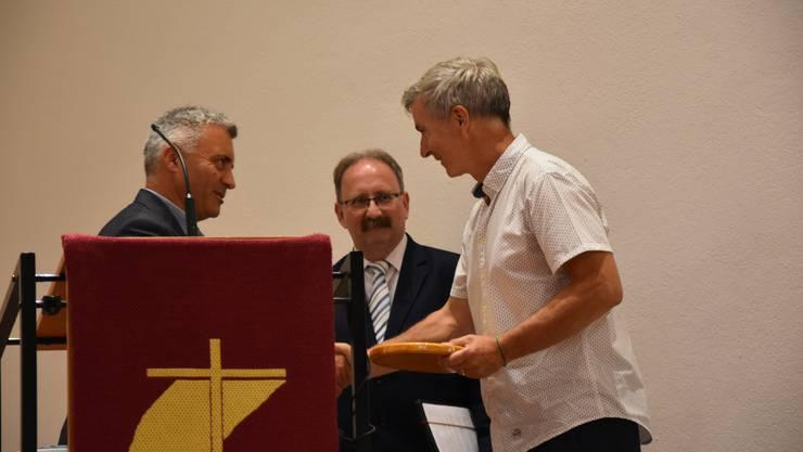 der ungar. Kirchenpflegepräsident überreicht dem Möhliner Kirchenpflegepräsident das Gastgeschenk (hinten Pfr. Bela Kalman aus Ungarn)