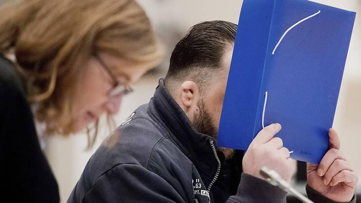 Der angeklagte Ex-Pfleger Niels Högel verdeckt sein Gesicht vor der Öffentlichkeit - er steht wegen 100 Morden an Patienten vor Gericht. (Archiv)