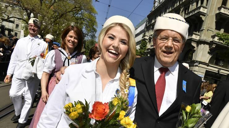 """Bundesrat Johann Schneider-Ammann (rechts) und Sängerin Beatrice Egli (links) im Hintergrund FDP-Praesidentin Petra Goessi, beim traditionellen Umzug, dem """"Zug der Zünfte""""."""