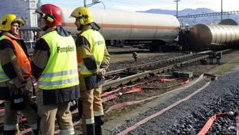 Feuerwehrleute inspizieren den umgekippten Zisternenwagen im Bahnhof Chiasso