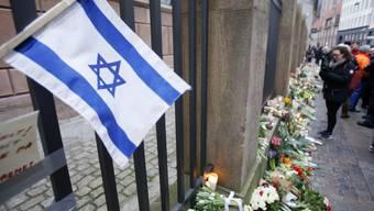 Blumen und eine israelische Flagge vor der Synagoge in Kopenhagen.