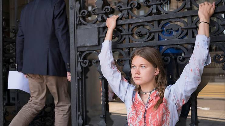 Eine Klimaaktivistin von Action ou Extinction hat sich ans Eingangstor des Parlamentsgebäudes gekettet am Rand der Sommersession der Eidgenössischen Räte.