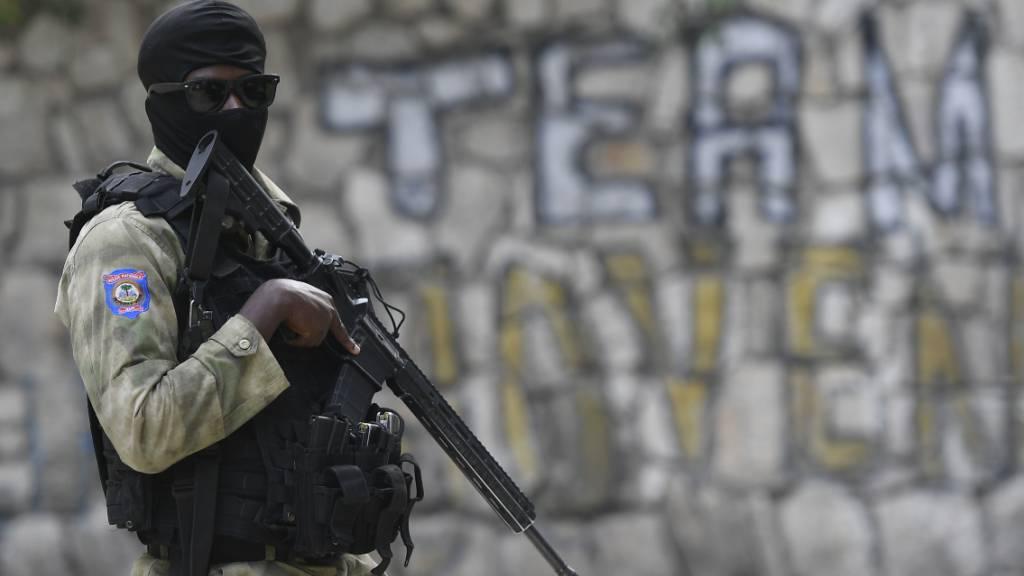 Ein haitianischer Polizist steht vor der Residenz des ermordeten haitianischen Präsidenten Jovenel Moise, während FBI-Agenten das Innere des Hauses inspizieren. Foto: Matias Delacroix/AP/dpa
