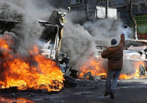 Ein Demonstrant wirft einen Stein Richtung Polizei.