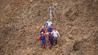 Retter im Schuttkegel des massiven Erdrutsches beim Dorf Pingdi in der chinesischen Provinz Guizhou. Mindestens 13 Menschen kamen ums Leben.