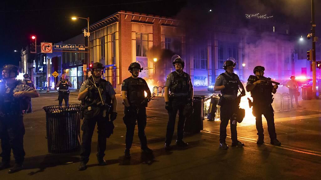 Die Polizei in Minneapolis steht Wache, nachdem Demonstranten nach einer Mahnwache für Winston Boogie Smith Jr. Müllcontainer auf der Straße in Brand gesetzt haben. Smith wurde am 3. Juni 2021 während einer Haftbefehlsaktion von Polizeibeamten erschossen.