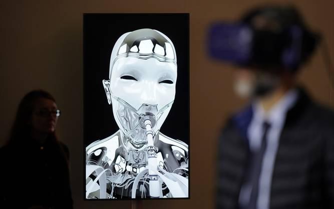 Besucher trägt virtueller Brille neben einer Videowand.